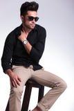 Le jeune homme assis avec la main a remplié dedans la chemise Images stock