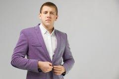 Le jeune homme attache la veste cramoisie d'isolement sur un fond clair photos libres de droits