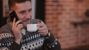 Le jeune homme attirant heureux de portrait repose le téléphone d'utilisation en café Homme bel s'asseyant avec le smartphone à l banque de vidéos