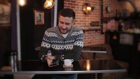 Le jeune homme attirant heureux de portrait repose le téléphone d'utilisation en café Homme bel s'asseyant avec le smartphone à l clips vidéos