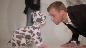 Le jeune homme attirant joue avec le bébé sur le plancher sur le fond des personnes de danse banque de vidéos