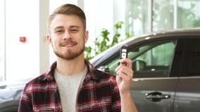 Le jeune homme attirant souriant tenant la voiture verrouille la pose au concessionnaire des véhicules à moteur banque de vidéos