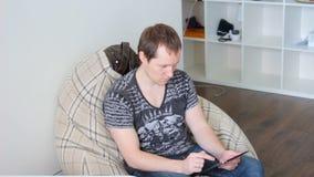 Le jeune homme attirant utilise le comprimé se reposant dans la maison clips vidéos