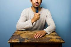 Le jeune homme au bureau parle dans le microphone Photos libres de droits