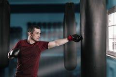 Le jeune homme aux cheveux courts s'exerce dans un gymnase avec un sac de sable image stock