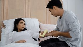 Le jeune homme avait l'habitude la serviette pour que son épouse réduise la fièvre Photo stock