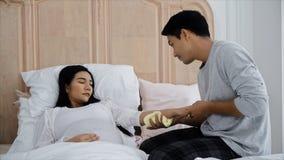 Le jeune homme avait l'habitude la serviette pour que son épouse réduise la fièvre Photos stock