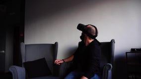Le jeune homme avancé employant l'instrument spécial et l'application augmentée de réalité s'assied en navigateur et regarde le f