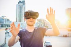 Le jeune homme avec des mains a augmenté devant lui appréciant le casque en verre de réalité virtuelle sur le fond du paysage de  Images libres de droits