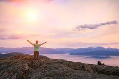 Le jeune homme avec des mains dans le ciel se tenant sur la falaise de la roche Photo stock