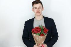 Le jeune homme avec des tulipes, bouquet de ressort fleurit Photo stock