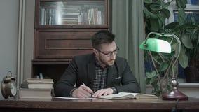 Le jeune homme avec des verres a focalisé le livre de lecture et prendre le bureau de notes à la maison banque de vidéos