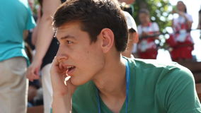 Le jeune homme avec l'insigne parle au téléphone portable parmi des spectateurs banque de vidéos