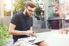 Le jeune homme avec la barbe de hippie travaille dehors sur l'ordinateur portable tout en se reposant dans la place de ville Image stock