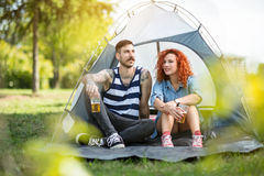Le jeune homme avec la fille rousse bouclée repose et boit de la bière dedans Photos stock