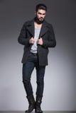 Le jeune homme avec la longue barbe tient le collier de son manteau photo libre de droits