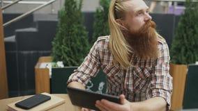 Le jeune homme avec la tablette se reposant en café ayant dehors détendent et reste du travail banque de vidéos
