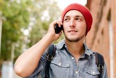 Le jeune homme avec le chapeau rouge fait appel à son téléphone portable Image libre de droits