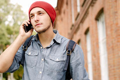 Le jeune homme avec le chapeau rouge fait appel à son téléphone portable Images stock