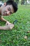 Le jeune homme avec magnifient le verre photo stock