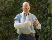 Le jeune homme avec un bras a moulé le service de mini-messages à son téléphone Image stock