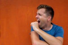 Le jeune homme baîlle avec la fatigue, couvrant sa bouche de sa main Il ` s ennuyé Image libre de droits