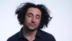 Le jeune homme barbu charismatique dans la chemise noire sur le fond blanc montre différentes émotions banque de vidéos