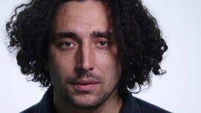 Le jeune homme barbu charismatique dans la chemise noire sur le fond blanc montre différentes émotions clips vidéos