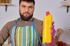 Le jeune homme barbu dans la cuisine fait la publicité Il favorise le détergent, le tenant dans une main et expositions à la camé images stock