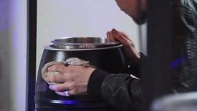 Le jeune homme barbu dans la veste noire essuie le petit burrell métallique avec le tissu clips vidéos