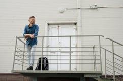 Le jeune homme barbu dans les jeans et la chemise de denim se tient sur le porche du bâtiment industriel près de la porte fermée  photo stock
