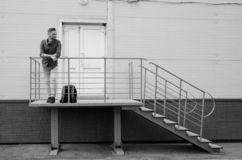 Le jeune homme barbu dans les jeans et la chemise de denim se tient sur le porche du b?timent industriel pr?s de la porte ferm?e  images stock