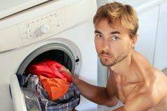 Le jeune homme beau charge la blanchisserie dans la machine à laver Femme au foyer masculine, concept de célibataire images stock