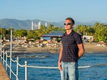 Le jeune homme beau dans des lunettes de soleil se tient sur un pilier sur le backgro Image stock