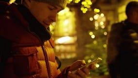 Le jeune homme beau dans la veste rouge utilise son smartphone le soir contre l'illumination de Noël Tiré sur l'appareil-photo RO clips vidéos