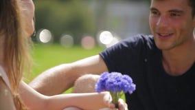 Le jeune homme beau donne à son amoureux un bouquet des fleurs dans le mouvement lent banque de vidéos