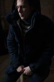 Le jeune homme beau fume la cigarette dans l'obscurité - photographie Image stock