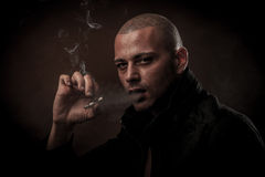 Le jeune homme beau fume la cigarette dans l'obscurité - photographie de Image stock