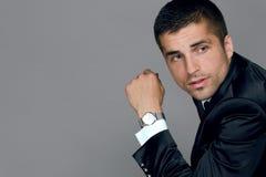 Le jeune homme beau utilise une montre Photos stock