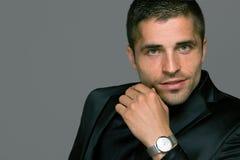 Le jeune homme beau utilise une montre images libres de droits