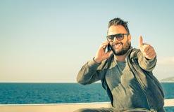 Le jeune homme bel avec des pouces se lèvent et smartphone Image libre de droits