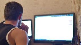 Le jeune homme bel avec le hippie de plein-barbe travaille à l'ordinateur de bureau à la maison ou dans le bureau clips vidéos