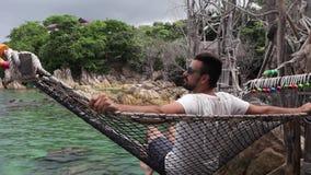 Le jeune homme bel balance dans l'hamac avec une vue de mer banque de vidéos