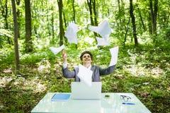 Le jeune homme bel d'affaires au bureau de table de travail avec l'ordinateur portable dans la forêt verte avec des frais générau Photo stock