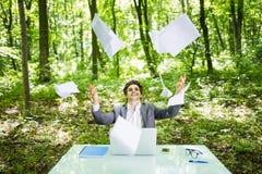 Le jeune homme bel d'affaires au bureau de table de travail avec l'ordinateur portable dans la forêt verte avec la mouche empaque Images stock
