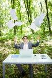 Le jeune homme bel d'affaires au bureau de table de travail avec l'ordinateur portable dans la forêt verte avec la mouche empaque Image stock