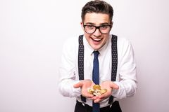 Le jeune homme bel d'affaires est les verres et la main blanche de chemise retardant le bitcoin d'or et le bitcoin d'argent dans  photo libre de droits
