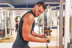 Le jeune homme bel fait le lat tirent vers le haut l'exercice dans le gymnase photos stock