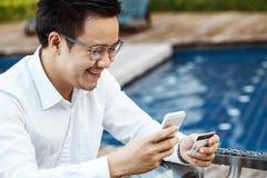 Le jeune homme bel ont plaisir à faire des emplettes en ligne au téléphone portable avec du Cr Image stock