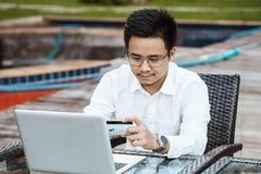Le jeune homme bel ont plaisir à faire des emplettes en ligne au téléphone portable avec du Cr Image libre de droits